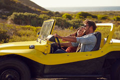 Smiling couple going on holidays together on a summer day. Young men with his girlfriend on  road trip in a buggy car Stock Images