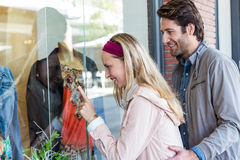 Smiling couple going window shopping and pointing at clothes Royalty Free Stock Photos