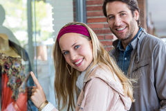 Smiling couple going window shopping and pointing at clothes Stock Photography