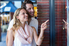 Smiling couple going window shopping and pointing at window Royalty Free Stock Image