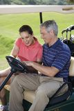 Smiling couple in golf cart Royalty Free Stock Photos