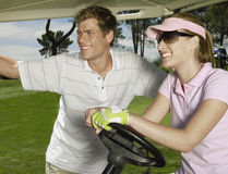 Smiling Couple In Golf Cart. Smiling young couple in golf cart Stock Image