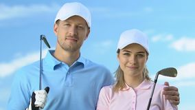 Smiling couple of golfers posing with clubs against blue sky, golf club trainers stock video