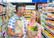 Smiling couple with grocery bags Stock Photos