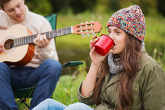 Smiling couple with guitar in camping Stock Photography
