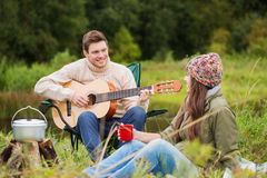 Smiling couple with guitar in camping