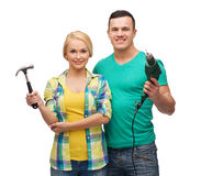 Smiling couple with hammer and drill Royalty Free Stock Photos