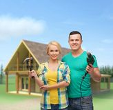 Smiling couple with hammer and drill Royalty Free Stock Photography