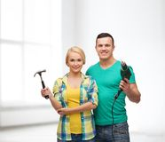 Smiling couple with hammer and drill. Repair, construction and maintenance concept - smiling couple with hammer and drill over white background Royalty Free Stock Photo