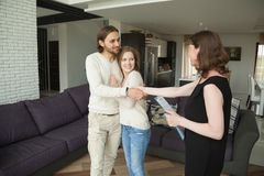 Smiling couple handshaking real estate agent buying or renting h. Smiling young couple handshaking real estate agent buying or renting new home, satisfied stock image