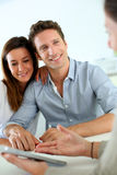 Smiling couple happy to buy new home. Young couple meeting financial adviser Stock Images