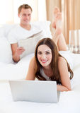 Smiling couple having activities lying on bed Stock Image