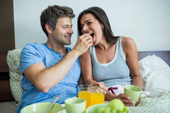 Smiling couple having breakfast on bed Stock Photo