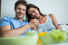 Smiling couple having breakfast on bed Stock Photography