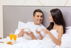 Smiling couple having breakfast in bed in hotel Royalty Free Stock Photography