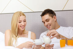 Smiling couple having breakfast in bed in hotel Royalty Free Stock Images