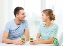Smiling couple having breakfast at home. Food, home, couple and happiness concept - smiling couple having breakfast at home stock images