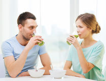 Smiling couple having breakfast at home. Food, home, couple and happiness concept - smiling couple having breakfast at home royalty free stock image