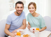 Smiling couple having breakfast at home stock images