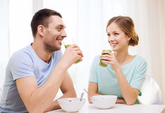 Smiling couple having breakfast at home. Food, home, couple and happiness concept - smiling couple having breakfast at home royalty free stock photography