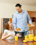 Smiling  couple having breakfast with juice Royalty Free Stock Photos