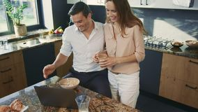 Smiling couple having breakfast at kitchen. Wife preparing food for busy husband stock footage