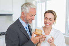 Smiling couple having breakfast in the morning before work Stock Images