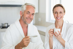 Smiling couple having coffee at breakfast in bathrobes Royalty Free Stock Photos