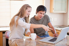 Smiling couple having coffee while using a laptop Stock Image