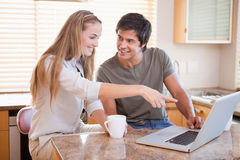Smiling couple having coffee while using a notebook Stock Photos
