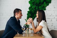 Smiling couple having dinner and drinking white wine at date in restaurant. Leisure, celebration, food and drinks, people and holidays concept - smiling couple Royalty Free Stock Images