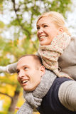 Smiling couple having fun in autumn park. Love, relationship, family and people concept - smiling couple having fun in autumn park Stock Photography