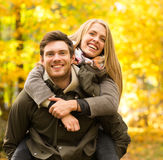 Smiling couple having fun in autumn park. Love, relationship, family and people concept - smiling couple having fun in autumn park Stock Photo