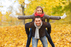 Smiling couple having fun in autumn park. Love, relationship, family and people concept - smiling couple having fun in autumn park Stock Images