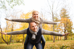 Smiling couple having fun in autumn park. Love, relationship, family and people concept - smiling couple having fun in autumn park Royalty Free Stock Images