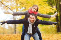 Smiling couple having fun in autumn park. Love, relationship, family and people concept - smiling couple having fun in autumn park Stock Image