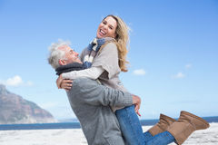 Smiling couple having fun on the beach in warm clothing Royalty Free Stock Image
