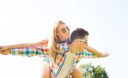Smiling couple having fun in park. Holidays, vacation, love and friendship concept - smiling couple having fun in park Royalty Free Stock Photography