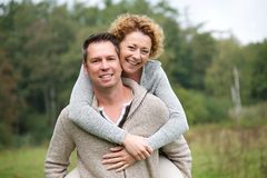 Smiling couple having fun with piggyback ride Royalty Free Stock Photo