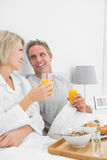 Smiling couple having orange juice at breakfast in bed Stock Image