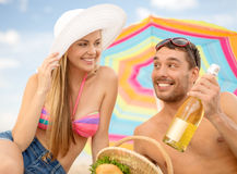 Smiling couple having picnic on the beach Stock Photography