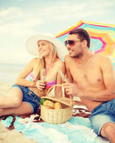 Smiling couple having picnic on the beach Stock Photo