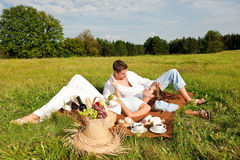 Smiling couple having picnic in summer meadow Royalty Free Stock Photography