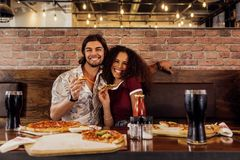 Smiling couple having pizza at cafe royalty free stock image