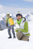Smiling couple having snowball fight in on mountain top together Royalty Free Stock Image