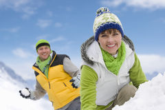 Smiling couple having snowball fight in snow together Royalty Free Stock Photography