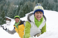 Smiling couple having snowball fight in snow together Stock Photography