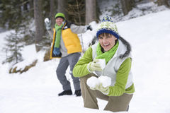 Smiling couple having snowball fight in woods together Royalty Free Stock Images