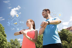 Smiling couple with heart rate watches outdoors Stock Images