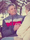 Smiling couple heats palms with each other. In park sunny cool day Royalty Free Stock Photos